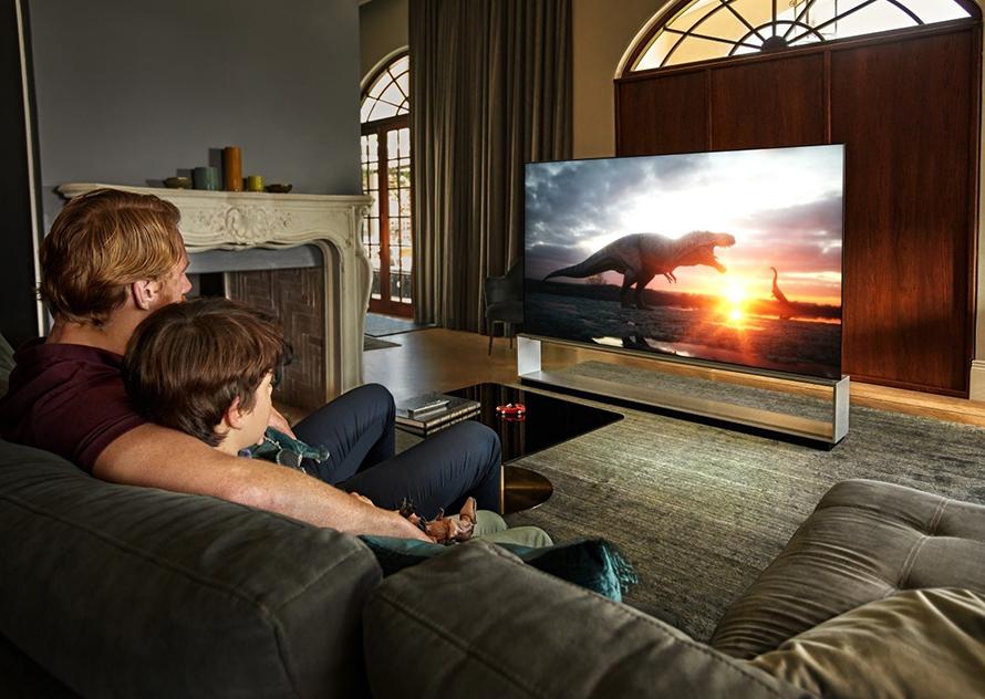 집안 거실에서 LG 올레드 TV를 즐기는 가족의 모습