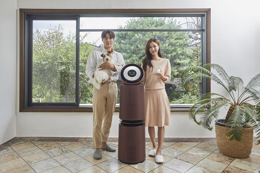 모델들이 신제품(사진 왼쪽)과 함께 집안 공기질 관리가 집중적으로 필요한 곳에 두고  사용하는 인공지능 센서를 소개하고 있다.