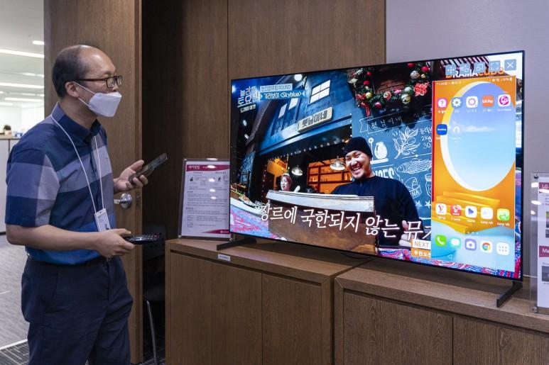2021년형 LG전자 스마트 TV의 리모컨과 스마트폰 연동 모습. 스마트폰을 TV리모컨에 가져다 대면 NFC를 통해 서로 연동되어 스마트폰의 화면을 TV화면으로 바로 감상할 수 있다