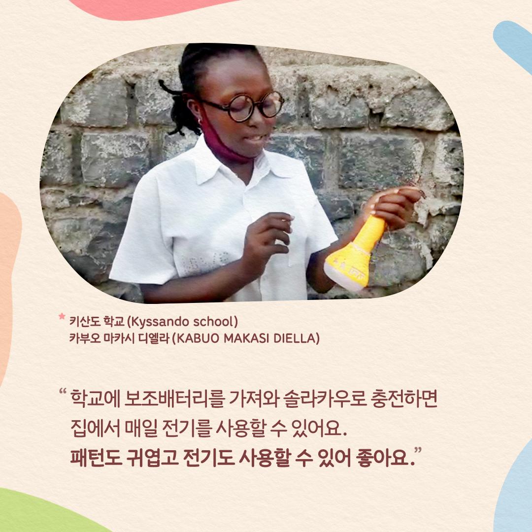 """솔라밀크를 들고 있는 콩고민구공화국의 아이(키산도 학교에 다니는 카부오 마카시 디엘라 학생 인터뷰 """"학교에 보조배터리를 가져와 솔라카우로 충전하면 집에서 매일 전기를 사용할 수 있어요. 패턴도 귀엽고 전기도 사용할 수 있어 좋아요."""")"""
