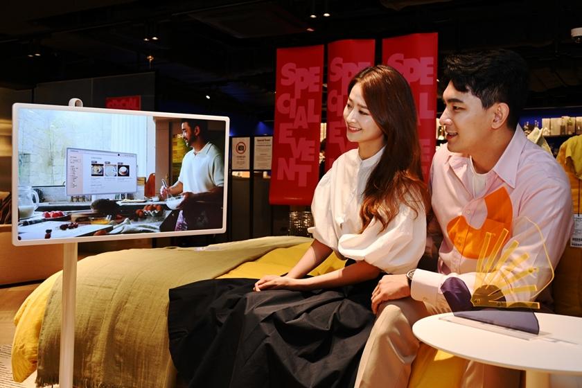 모델들이 매장에 전시된 LG 스탠바이미를 살펴보고 있다.