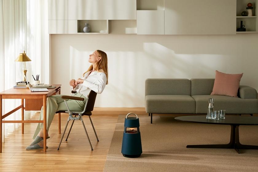 모델이 의자에 앉아 LG 엑스붐 360(모델명: RP4)로 음악을 감상하고 있다.