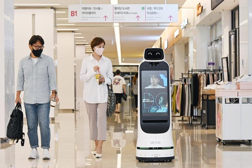 코엑스몰을 방문한 고객들이 LG 클로이 가이드봇을 바라보고 있다.