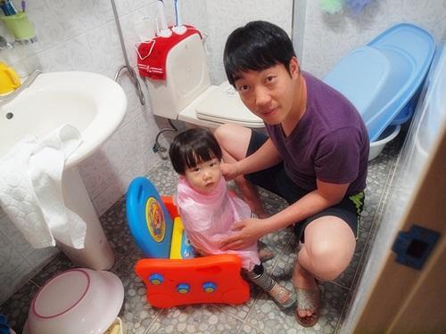 아버지가 어린 아이의 이발을 위에 화장실에 앉아있는 부자의 모습