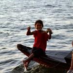 배위에 앉아서 해맑게 웃고있는 캄보디아 아이의 사진