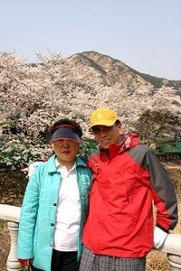 벚꽃이 보이는 전망에서 다정하게 어깨동무를 하고 있는 노부부