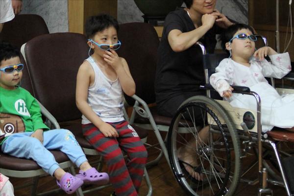 아이들이 뽀로로 3D 안경을 쓰고 관람하는 모습