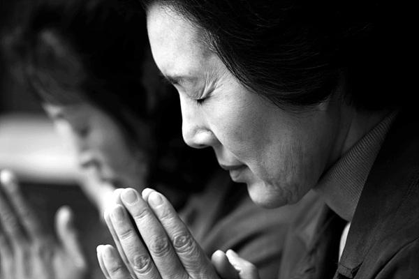 어머니가 기도하고 있는 흑백 사진