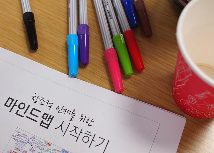 마인드맵 강의를 위한 색색깔의 사인펜들과 그 밑으로 이 날의 행사를 설명하는 종이가 있다.ㅣ