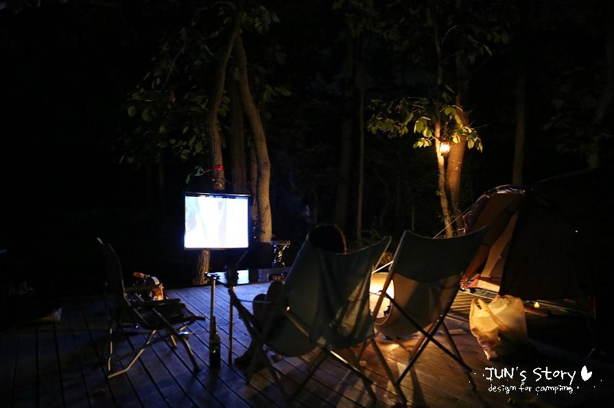 한밤 중 캠핑장에 LG 미니빔 TV를 스크린에 연결하여 영상이 재생되는 모습이다. 스크린 앞으로 캠핑 의자가 서너개 세워져 있고, 컴컴한 캠핑장 뒷편으로 나무들이 어스름하게 보이고 있다.