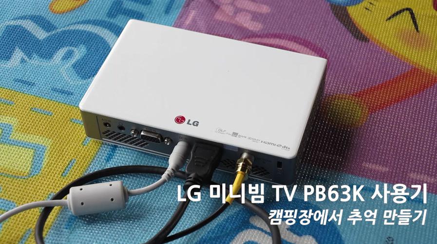 캠핑장 내 바닥에 설치된 매트 위에 LG 미니빔 TV가 놓여져 있는 모습이다. 본체 뒷편에 각종 전선이 꽂혀져 있다.