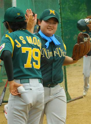 하이파이브를 하는 여자 야구선수들의 모습