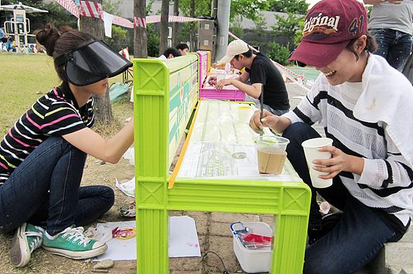 공원 의자에 그림을 그리는 LG전자 디자이너들