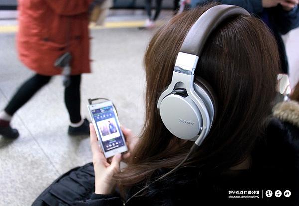 스마트폰으로 음악 듣고 있는 모습