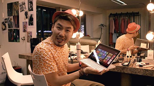 거울 앞에서 주황색 호피무늬 티셔츠와 오렌지 빛깔 모자를 쓴 노홍철이 LG 탭북을 들고 설명하는 모습이다