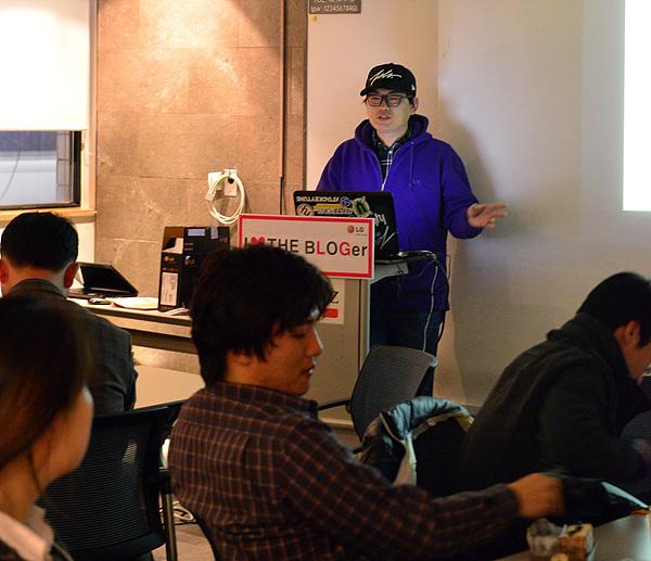 강의대에 서 있는 엄승주 감독님의 모습이다. 보라색 후드점퍼와 모자를 쓴 감독님은 스크린 앞에서 발표를 하고 있다.