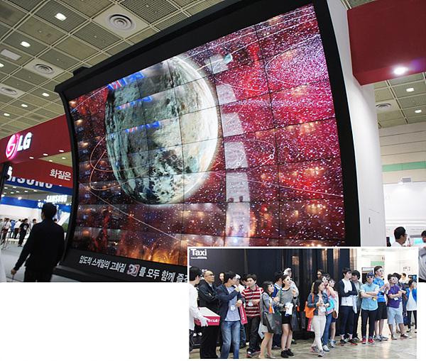 대형 스크린에 펼쳐진 LG 시네마 3D 영상의 모습이다. 수많은 관람객들이 스크린 앞에 서서 화면을 응시하고 있다.
