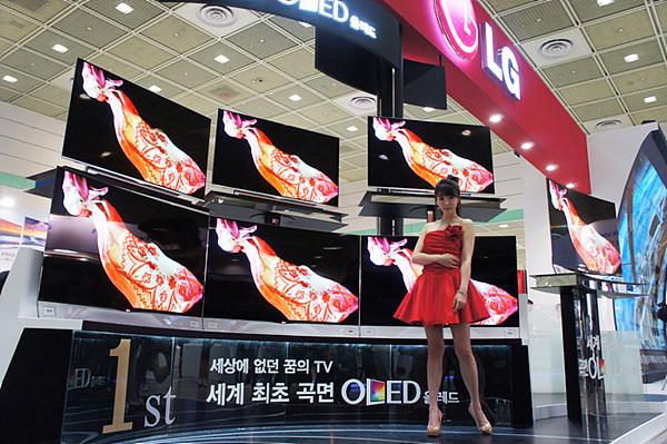 세계 최초 곡면 OLED TV가 7대 전시되어 있는 가운데 여자 모델이 포즈를 취하고 있다.