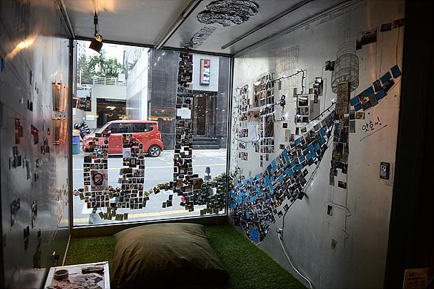 포켓포토로 출력한 사진을 가지고 사면으로 둘러쌓인 벽면 가득 사진이 붙여져 있는 모습이다 완성 전