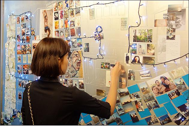 포켓포토로 출력한 사진을 가지고 사면으로 둘러쌓인 벽면 가득 사진을 붙이고 있는 여성의 뒷보습이 보인다