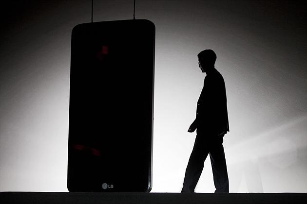 LG G2 런칭 행사가 시작하며 LG G2가 보이는 화면 앞으로 발표자가 입장하는 모습이 보인다.