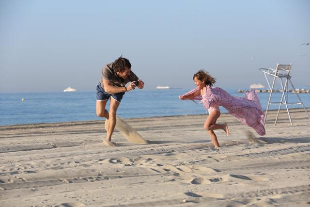 LG G2 광고 촬영 중 해변에서 성인 남자 배우가 여자 아역 배우가 뛰어 노는 모습을 촬영하고 있다.
