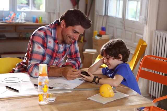 LG G2 광고 촬영 중 성인 남자 배우와 남자 아역 배우가 휴대폰을 보며 웃고 있다.