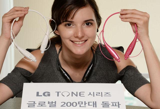 모델이 'LG TONE+'를 들고 포즈를 취하고 있다.