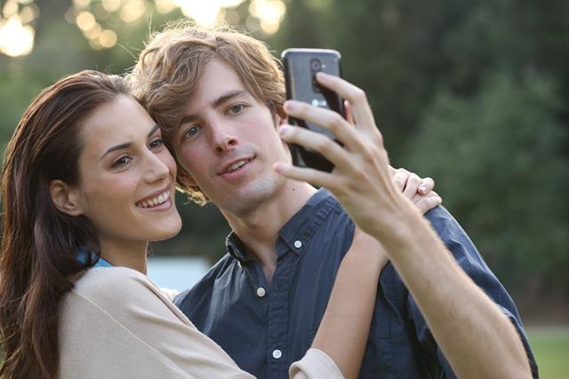 LG G2 광고 중 남녀 배우가 후면 키를 이용하여 셀프카메라를 찍고 있다.