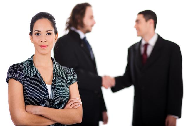 양복을 입은 두 남자가 대화를 하고 있고 그 앞에 한 여자가 팔짱을 끼고 앞을 바라보고 있다.