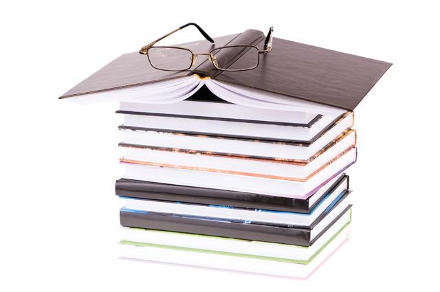 여러 권의 책이 쌓여 있고 그 웨 펼쳐진 책과 안경이 놓여 있다.