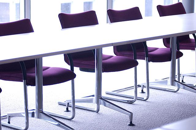 일자로 된 긴 테이블에 보라색 의자가 쭉 나열되어 있다.