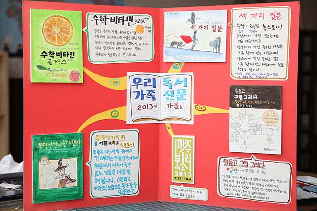 완성된 가족독서신문으로 빨간 판 위에 책에 관한 정보들이 적혀 있다.