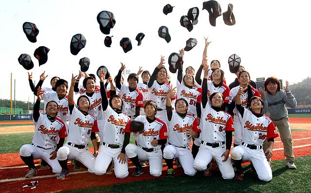 승리의 기쁨을 만끽하는 일본 대표팀이 잔디밭에 앉아 쓰고있던 모자를 던지며 환호하고있는 모습이다