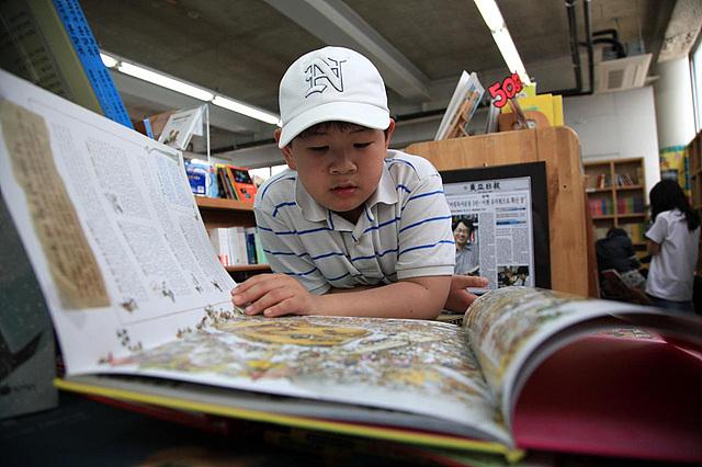 흰 모자를 쓴 아이가 큰 책을 펼쳐 유심히 읽고 있는 모습이다.