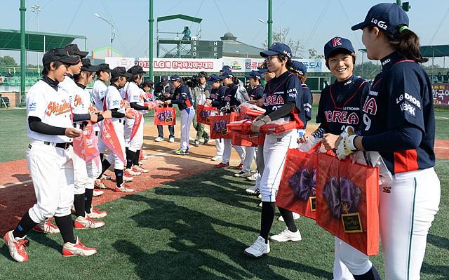 한-일 여자 야구 대표팀이 서로 나란히 마주보고 서서 선물을 교환하고 있다