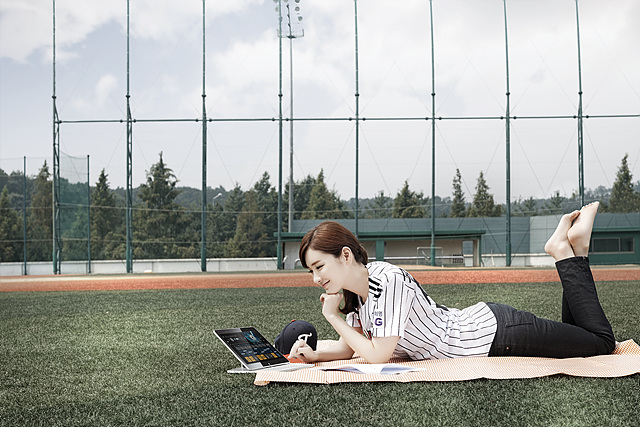탭북을 보며 잔디밭에 누워 있는 공서영 아나운서의 모습이다.