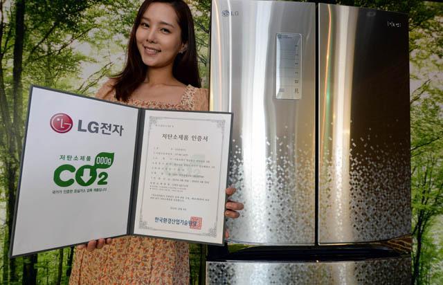 LG전자 김치냉장고 '디오스 김치톡톡(모델명: R-D413PFSM 포함)' 신제품이 김치냉장고 업계 최초로 '저탄소제품인증'을 받았다. 인증을 받은 제품 앞에서 모델이 포즈를 취하고 있다.