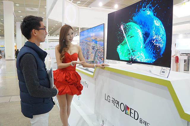 전시된 LG 곡면 올레드 티비를보는 관람객과 모델이 설명을해주고 있다