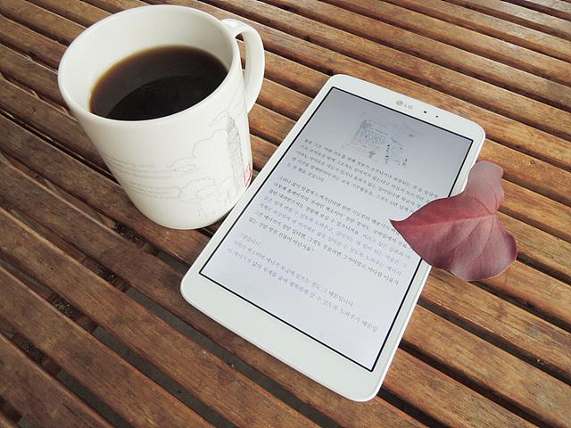 나무로 된 테이블 위에 G패드가 놓여 있고 그 옆엔 커피가 담긴 하얀 머그잔이 있다.