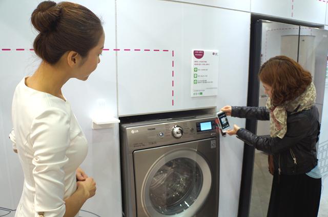 그린 홈 내부에 전시된 트롬 세탁기를 휴대폰으로 촬영하는 관람객의 모습이다