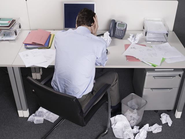 컴퓨터 책상 앞에서 두 손으로 귀를 막고 고개를 숙인 채 있는 남자의 뒷 모습으로 상당한 스트레스를 받은 것처럼 보인다.