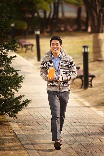 HE사업본부 Media 부품보증팀 홍준영 사원이 아이보리색 스트라이프가 들어간 가디건을 입고 오렌지색 수첩을 들고 걷고있다