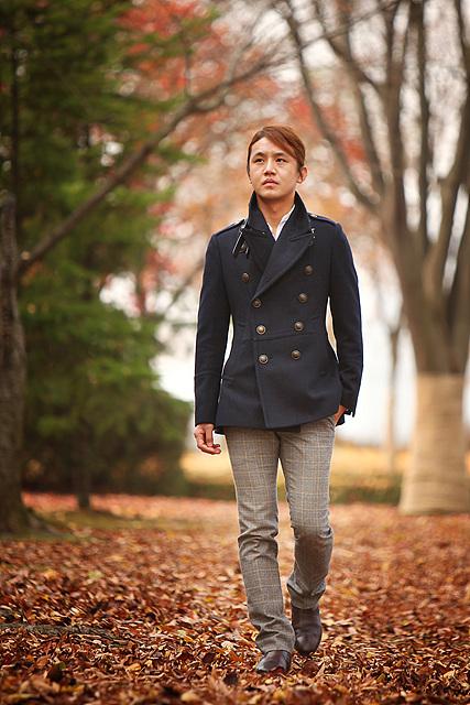 COO 실장기술팀 이철 사원이 블랙 코트에 스트라이프가 들어간 그레이컬러 바지를 입고 낙엽 길을 걷고 있따