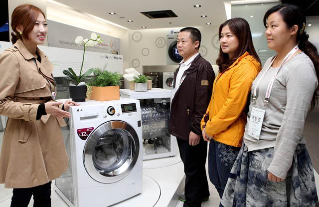 'LG베스트샵 부산본점'을 방문한 중국 유통 딜러들이 블랙라벨 세탁기, 사각 로봇청소기 등 최신 프리미엄  가전 제품을 유심히 살펴보고 있다.