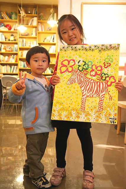 아이들이 얼룩말 그림을 들고 포즈를 취하고 있다.