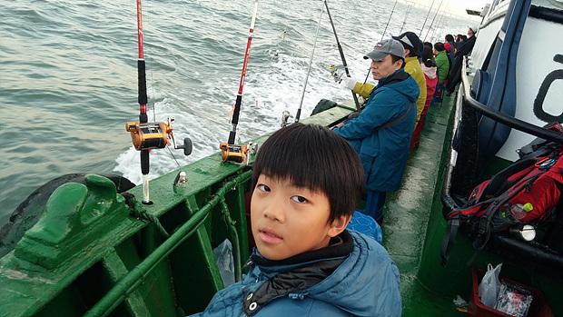 바다 낚시에 같이 간 아들이 배 위에서 기념촬영을 하고있다