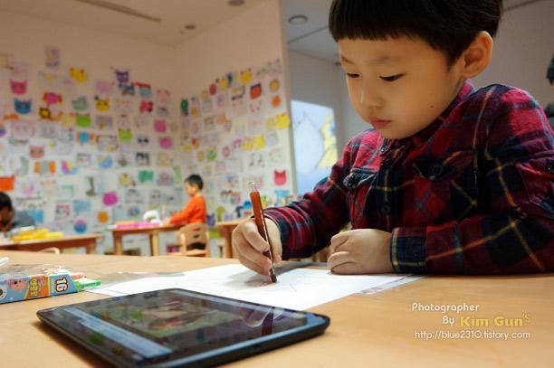 아이가 G Pad 8.3에 나온 그림을 따라 그리고 있다.