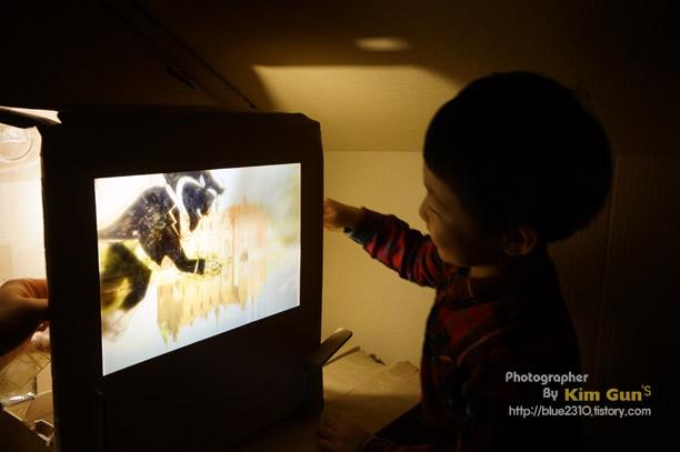 종이와 빛을 이용해 아이랑 그림자 놀이를 하고 있는 모습이다.