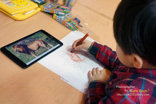 G Pad 8.3으로 사자 그림을 켜놓고 아이가 종이에 따라그리고 있다.